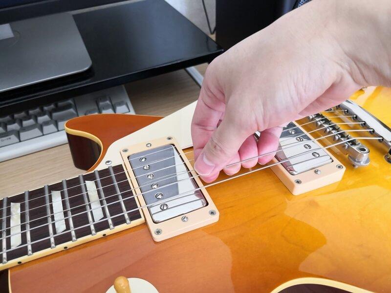 手で弦を引っ張って伸ばす