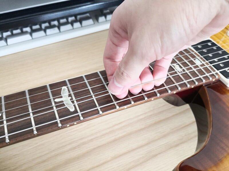 弦を手で引っ張って伸ばす