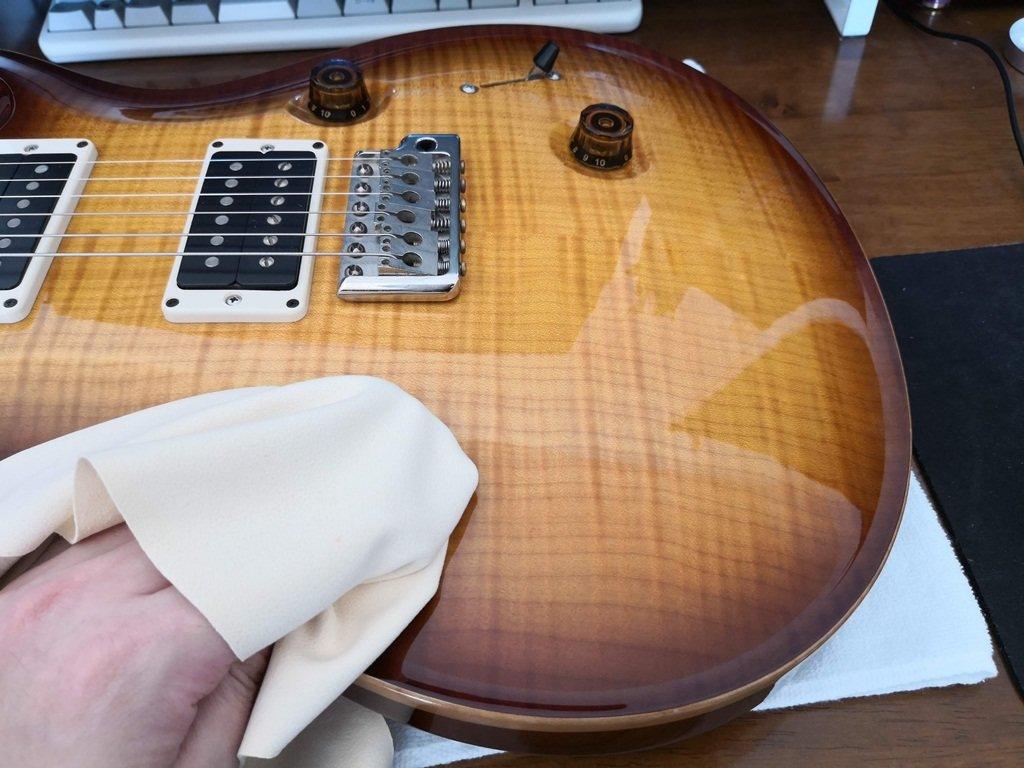 ギターのボディをセーム革のクロスで磨く様子