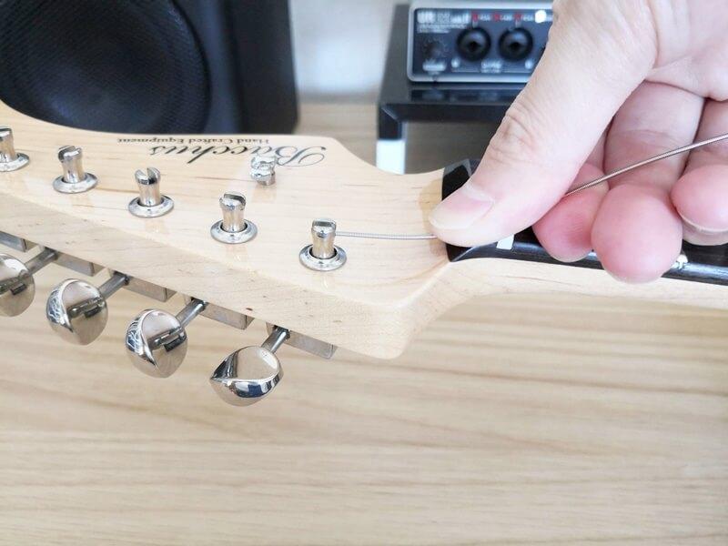 弦をを押さえ、ペグを回す