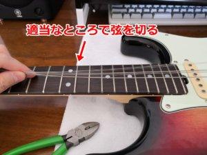 古い弦を真ん中で切る