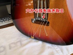 古い弦をボディ裏から抜き取る