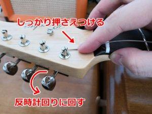 弦を押さえながらペグを回す