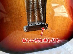 新しい弦をボディ裏から差し込む