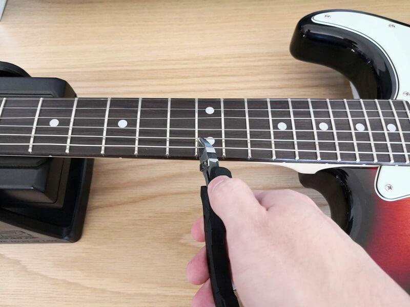 古い弦をニッパーで切る