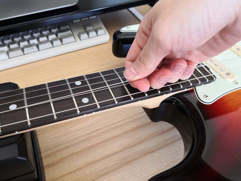 弦を手で引っ張る