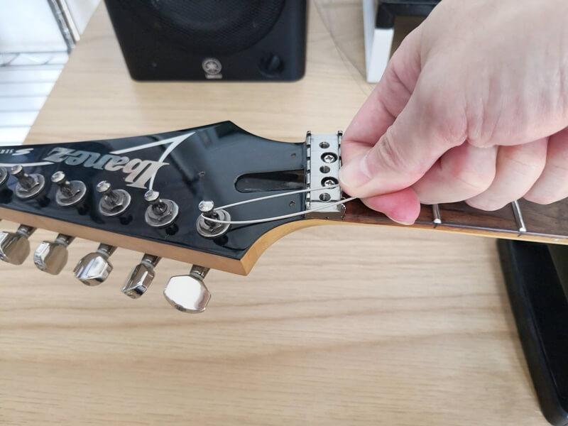 弦を引っ張りながらペグを回す