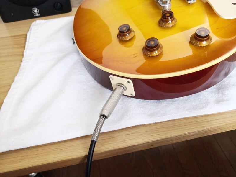エレキギターにシールドを挿す